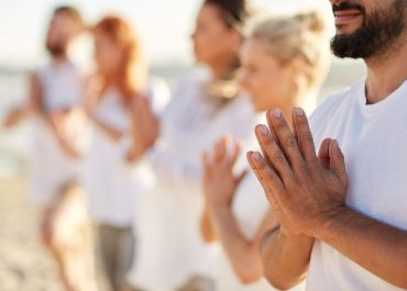 yoga, fitness, sport and healthy lifestyle concept - group of people meditating on beach